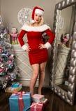 性感圣诞节女孩摆在 作为在照相机前面的圣诞老人打扮的白肤金发的妇女 库存照片