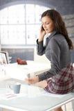 性感女实业家聊天的办公室的电话 免版税库存图片