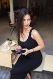 年轻性感女性工作在她的在午休期间的触摸板,当坐在餐馆户外时 免版税图库摄影