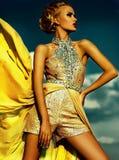性感时髦白肤金发在蓝天后的黄色birght礼服 免版税库存照片