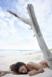 性感深色睡觉在海滩的沙子 免版税库存照片
