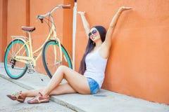 性感的亚裔妇女坐在墙壁附近的和葡萄酒骑自行车 图库摄影