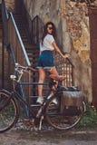 性感的亭亭玉立的女孩穿着短的牛仔布短裤的和摆在台阶的一件白色T恤杉,当站立在城市自行车附近时 库存照片