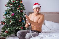 性感的人在戴在圣诞节概念的床上圣诞老人帽子 免版税库存照片