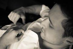 性感的人解扣他的衬衣,当坐在扶手椅子时 图库摄影