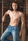 性感的人赤裸上身在牛仔裤在谷仓临近木梯子 免版税图库摄影