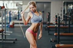 性感的体育穿戴的健身愉快的白肤金发的女孩与在微笑的健身房的完善的身体摆在和 免版税库存照片