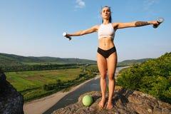 性感的做与哑铃的适合深色的妇女锻炼室外 训练在山峰 绿色山 免版税库存图片