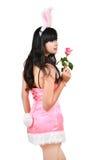 性感的兔宝宝女孩暂挂粉红色玫瑰 免版税库存照片