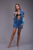 性感的典雅的美好的妇女上面模型在与夹克被取消的和可看见的胸罩女用贴身内衣裤,肉欲的看看的一套蓝色衣服站立c 免版税库存照片
