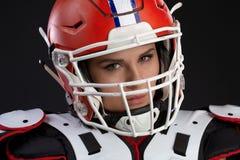 性感的可爱的女孩画象有明亮的构成的在橄榄球的体育成套装备与在强烈看的头的盔甲 库存照片