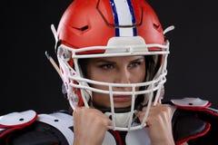 性感的可爱的女孩画象有明亮的构成的在橄榄球的体育成套装备 免版税库存照片