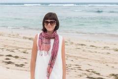 年轻性感的可爱的妇女画象白色礼服的有丝绸围巾的单独在热带海滩巴厘岛 免版税图库摄影