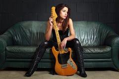 性感的吉他演奏员坐长沙发 库存图片