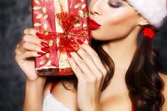 性感的圣诞老人妇女亲吻的礼物 免版税图库摄影