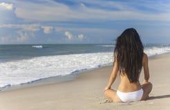 性感的在海滩的妇女女孩坐的比基尼泳装 库存图片