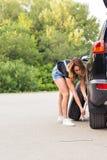 性感的在路旁的妇女变速轮 库存图片