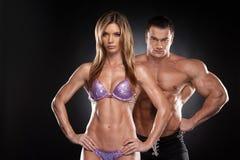 性感的夫妇适合男人和妇女显示肌肉。 免版税库存照片
