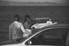 性感的夫妇 在爱的夫妇站立近的银色汽车,背景的海 夫妇在度假,蜜月到达了 人和 库存照片