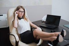 性感的女商人与她的脚坐书桌 库存图片