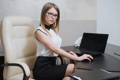 性感的女商人坐在书桌在办公室 库存图片