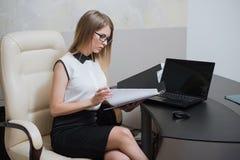 性感的女商人坐在书桌在办公室 库存照片