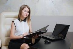 性感的女商人坐在书桌在办公室 免版税图库摄影