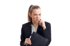 性感的女商人看起来去,并且叮咬您的手指在白色背景被隔绝 免版税库存图片
