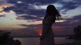性感的女孩剪影燕尾服的在日落天空背景 美好的女孩跳舞和有乐趣在 影视素材