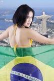 性感的女孩在城市拿着巴西的旗子 免版税库存照片