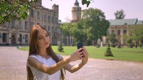 性感的女孩在智能手机做selfie在公园自白天在夏天,通信概念 股票录像