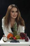年轻性感的女孩在立场倾斜了,并且微笑接近assorti differen在黑背景的果子 免版税库存照片