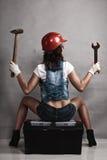 性感的女孩技工与工具一起使用 backarrow 库存图片