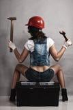 性感的女孩技工与工具一起使用 backarrow 图库摄影