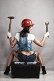性感的女孩技工与工具一起使用 backarrow 免版税库存照片