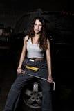 性感的女孩技工坐轮胎在他的手上的拿着一把板钳 无色的生活概念 免版税库存图片