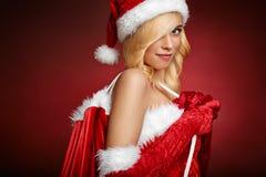 性感的女孩拿着圣诞老人礼品袋子 免版税库存图片