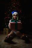 性感的女孩接受了礼物在圣诞树下 图库摄影