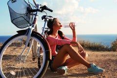 性感的女孩饮用水在自行车旁边坐海滩 库存照片