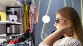 性感的女孩,尝试在太阳镜在一家时髦的商店,精品店和敬佩的高,美丽的白肤金发的妇女在前面 股票录像