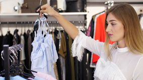 性感的女孩,高,美丽的白肤金发的妇女在商店选择衣裳 购物在一家时髦的服装店 慢的行动 股票视频