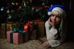 性感的女孩画象在与礼物的圣诞树下 库存照片