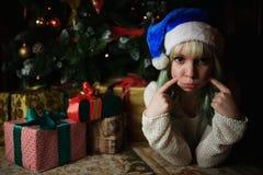 性感的女孩画象在与礼物的圣诞树下 免版税库存图片