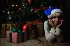 性感的女孩画象在与礼物的圣诞树下 免版税库存照片
