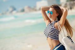 性感的女孩画象有海滩袋子的在海滩 库存照片