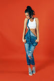 年轻性感的妇女佩带的牛仔裤工作服 现代便装样式 图库摄影
