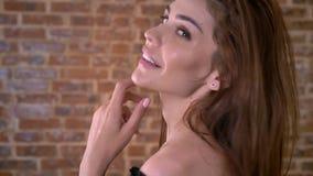 性感的妇女使用与头发,观看在照相机,调情的人概念,砖背景 股票视频