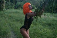 性感的妇女创造性的神色在棕榈树森林里隔绝的橙色假发的 库存照片