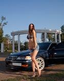 性感的妇女和大型高级轿车 免版税库存照片