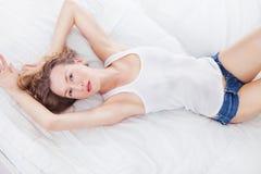 性感的妇女在牛仔布短裤和白色躺穿戴了在床上 库存照片